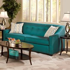 Get some Gatsby style in your living room! This transitional sofa comes in peacock blue and was made in the USA. Retro-sloped track arms, a 6-button back, and espresso brown pyramid legs accent the modern shape. 2 geometric-patterned accent pillows are the final touch. Mason Peacock Blue Sofa | Weekends Only Furniture and Mattress