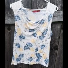 Elle Tank Top Size Large This beautiful cream colored Elle tank has a yellow, blue, and tan floral pattern. It also has a slight hanging neckline and thick lace shoulder straps. It is made of 100% rayon (exclusive of decoration). This size Large tank is gently used but is in excellent condition. It is the perfect addition to a summer wardrobe! Elle Tops Tank Tops
