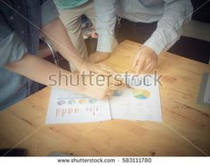 Close-up of female and male hands pointing at turnover graph while discussing it on wooden desk in office. group support concept.