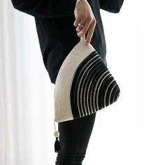 Our handle clutch is the perfect everyday bag or fancy evening clutch. Its unique shape will comfortably fit all your essentials and more. The bottom of the clutch is dyed in a black like tie dye pattern and the top is natural ivory. The bag comes with a zipper and a stylish tassel.  Mia Mélange bags are made from 100% cotton rope which we carefully sew together in a coiling technique. The cotton is grown locally in South Africa by farmers who are members of the Better Cotton Initiate (BCI). Tie Dye Patterns, Everyday Bag, Cotton Rope, Ikat, Clutch Bag, Tassels, Handle, Fancy, Essentials