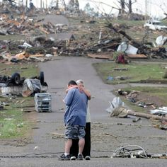 A mother comforts her son in Concord, Alabama, near his house which was completely destroyed by a tornado in April of 2011.