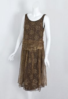 Metallic lace flapper dress, c.1925  The dress is fashioned from bronzed metallic lace over a black satin lining, which is attached to the lace at the neckline and armholes. The lining has a wide hem border of black chiffon.  The dress slips on without closures. The lower sides of the bodice are ruched, creating a cummerbund effect. The scalloped border on the lace is of the last degree of charm.