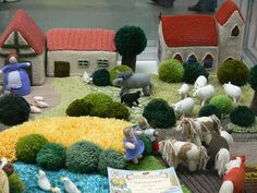 """A play farm inspired by the book """"The Knitted Farmyard"""" - can't say I'll ever make the animals and buildings, but making a simplified play mat using their ideas for bushes and grasses  would be a fun project."""