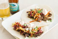 spicy korean beef tacos topped with sweet sesame slaw and Sriracha sour cream