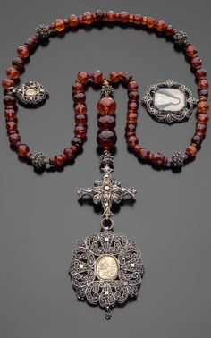 Rosary, Southern German, mid-17th century, 65.5 cm (25 13/16 in.), silver, silver gilt, amber, painted ivory, and glass. During the Middle Ages, rosaries were used by the religious orders and lay public to assist in the recitation of the Lord's Prayer. Known as paternoster beads, each strand consisted of 150 beads-one bead representing a Psalm. By the mid-twelfth century, prayer beads were also used in the recital of Ave Marias, a practice deemed particularly suitable for women.