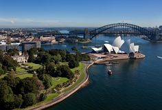 Sydney, New South Wales, Australia / The Royal Botanic Gardens and Government House beside Farm Cove in the foreground / Sydney Opera House, the other side of which lies Circular Quay and the Harbour Bridge.