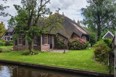 The picturesque house in a small village - Giethoorn, Netherlands: known for its bridges, waterways,  thatched cottages  and punters. It is also called the 'Dutch Venice' and known to the world Monopoly edition.