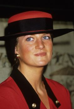 Princess Diana, wearing a red & black suit and a boater style Philip Somerville hat on a visit to Normandy in Caen, France September 9, 1987. A black 'snood' was attached to the back of the hat and trails down her back.
