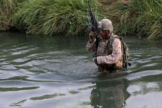 5th Marine Regiment wades through the water of an irritation canal to move into position. Sangin, Afghanistan.