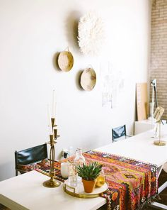 A modern dining room with fresh southwest style featuring woven basket wall decor, a large wood dining table, black leather side chairs, and a woven textile table runner - Dining Room Ideas & Decor - designsponge.com