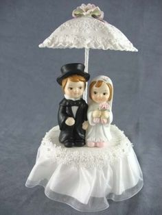 This cute rainy day cake topper features a white fine porcelain parasol umbrella accented with pastel colored porcelain roses over a cute child couple with the bride carrying a delicate handmade baby pink rose bouquet. Skirt is made of organza. Handpainted porcelain. Perfect for a rainy day wedding! <br /> <br />Please note: The hair color or colors you have ...