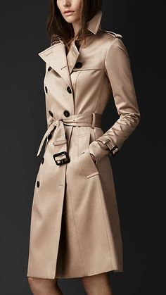 Long Cotton Sateen Trench Coat by: Burberry @Burberry (US) The trench coat is crafted from cotton sateen, which has a lustrous appearance and smooth texture. A closely cut design, the trench coat features set-in sleeves and a tapered waist. Heritage details include a gun flap, rain shield and belted cuffs.