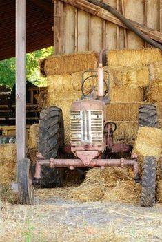 Old tractor in between bales of straw in a barn   What fun and deep learning could happen here for all children.  What is the straw?  How is it grown, harvested and baled?  How does the tractor help with this work and how was it done before tractors?
