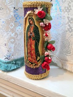 This altar candle has the image of Our Lady of Guadalupe framed in a sequin trim and purple glitter and trimmed on one side with vintage silk
