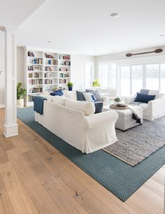 Lake House basement family room. White slipcovered couches, denim jute rug, and navy pillows and accents give a coastal feel to this cozy room.