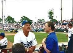 """Harsh, heartfelt words landing with shocking force: """"Pictured here: Jon and Tommy Lasorda talk baseball at Spring Training in Vero Beach, Fla. The full garish flowering of the baby boomers' vast sense of entitlement encompasses an entitlement to exemption from nature's mishaps, and to a perfect baby. So today science enables what the ethos ratifies, the choice of killing children with Down syndrome before birth. This is what happens to 90 percent of those whose parents have prenatal…"""