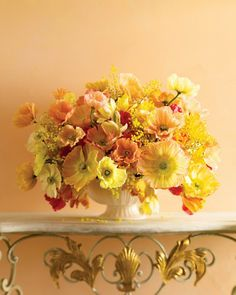 Paint Palettes - Choosing colors from the same tonal family results in a unified arrangement. But it's important to vary the forms and balance the amount of every color to bring out the best in each one, like with this vibrant bouquet of pink, orange, and yellow flowers against a subdued peach background.