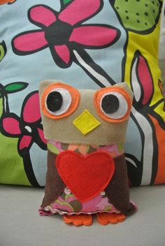 I handmade this little guy who has soft velour head, bright expressive felt eyes, floral body pattern, and holds a big heart in his wings.