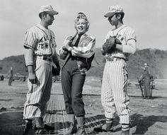 Two excited Korean baseball players pose with Marilyn Monroe in Feb. 1954