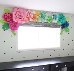 How to make giant 3 dimensional paper flowers using colored cardstock. A rainbow of paper flowers used as a window treatment. Whimsical, colorful DIY home decor.