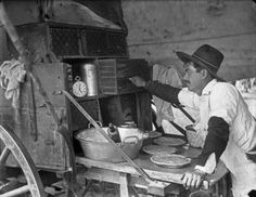 Mex John Making Pies. Vintage negative number : no number. Close-up view of XIT cook leaning over table extending from rear of wagon. There are pies, kitchen utensils, cookbook and clock on table. [1880-1900?] Photographer: L.A. Huffman. Catalog # 981-254