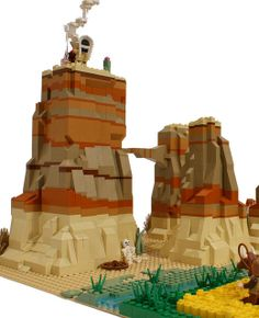 this Lego canyon scene is really amazing... i love how they built the canyon walls, including the different shades of reds and browns, i think my favorite part is the Native American at the top making smoke signals... it's awesome!! the lost wagon wheel and skeleton next to it is totally old western movie classicness!