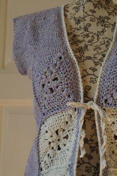 Vesta s háčkovanými čtverci Kombinace pletení a háčkovaní dala vzniknout této vestě v kombinaci levandulově-modrého melírua smetanové barvy. Zapínání je řešeno zavázáním dvěmi šňůrkami. Materiál: 100% bavlna. Velikost: 36/40