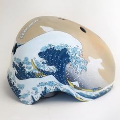 A hand-painted rendition of Hokusai's woodblock print The Great Wave off Kanagawa, adapted for the bicycle helmet, with an invented continuation of the landscap