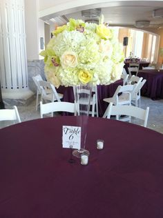 Luxe Petal flowers, light green roses, purple tulips, purple calla lilies, white roses, and hydrangeas.