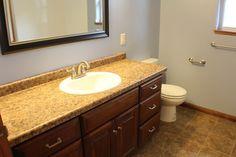(VC108) Pecan Floor Plan. Main Bathroom. Pionite Frederick Countertop. Square Raised Cabinets in CF-126 New Heritage Stain. Lakeview Cedar Tile Flooring.