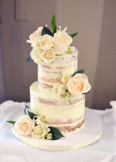 Nearly-naked two-tiered cake with cream-colored flowers