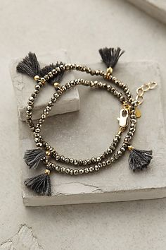 "Fluttered Tassel Wrap Bracelet - anthropologie.com -  pyrite, metal, cotton, 13"" long, .75"" tassels"