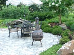 Paver Patio surrounded by lush landscaping and including Boulders and . Landscaping Backyard On A Budget, Landscaping Around Patio, Backyard Retreat, Landscaping With Rocks, Landscape Pavers, Small Garden Landscape, Landscape Design Plans, Landscape Arquitecture, Circular Patio