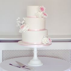 White wedding cake with piped royal dots & sugar roses, peony and gypsophelia