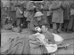 """THE BRITISH ARMY IN THE UK: EVACUATION FROM DUNKIRK, MAY-JUNE 1940  part of """"WAR OFFICE SECOND WORLD WAR OFFICIAL COLLECTION"""" (photographs) Made by: Puttnam (Mr) and Malindine (Mr)  A wounded soldier on a stretcher is given a drink on the quayside at Dover, 31 May 1940."""