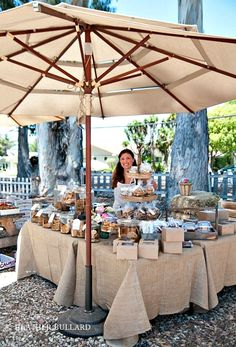 Farmer's market booth with burlap tablecloths and beige packaging and umbrella.
