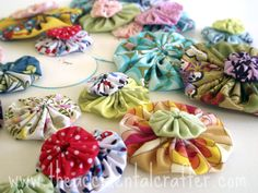 fabric yoyos  Cut out a circle, do a running stitch round the edge, pull, and flatten.  It's quick and easy! great on pillows, bags, bobby pins, and headbands,