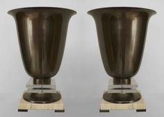 Pair of Art Deco gun metal torchere form up-light lamps resting on a pair of square Lucite panels above a square travertine base