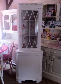 Shabby chic corner unit refurbished with Cath Kidston wallpaper inside top cupboard
