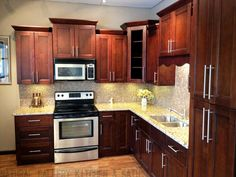 This Kitchen Features Brown Fantasy Leathered Quartzite Countertops Paired  With A Glass Tile Backsplash. It Also Has Beautiful White Cabinets And Au2026