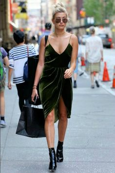 A woman with a sleeveless dark green velvet dress and black booties on walking down a busy street with a shopping bag