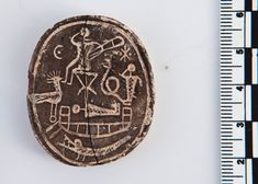 The amulet has several images. At the bottom, there is a mummy (likely the Egyptian god Osiris) wrapped in bandages, lying on a boat. Above the mummy, there is an image of Harpocrates, a god of silence, shown sitting on a stool. Harpocrates%u2019 right hand is raised up to his lips and there is a scepter in his left hand. To the right of Harpocrates there is a dog-headed creature called a cynocephalus that has a paw beside its lips, mimicking Harpocrates gesture. There is a snake between the…