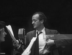 British stage and screen actor David Niven (1910 - 1983) adjusts his suspender as he reads a script and stands before a WNBC microphone while an unidentified woman in the foreground speaks, New York, late 1940s.