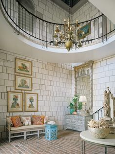 Entry to unique house in Jamaica. Love the limestone walls and brick floor. Love the antique French country bench and pillows, and the framed prints, plus the antique Italian commode and huge mirror. Charles Faudree