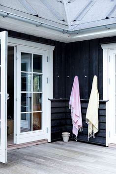 a beautiful way to hang those beach towels. summer house. black exterior.