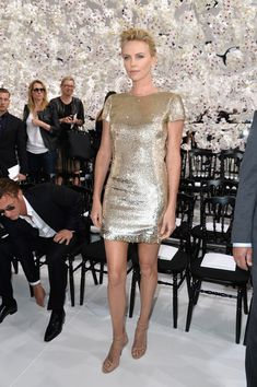 Charlize Theron stuns in a sparkly gold Dior mini at the Haute Couture runway show.