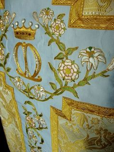 Real garnets and pearls embellish the crowned monogram on the back of the chasuble's cross -- a field of very pale blue silk.