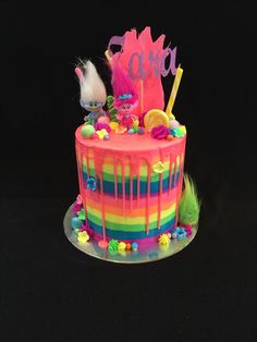 Trolls drip cake, with fluoro rainbow  icing and drips, chocolate poppy hair, lollipops, figurines of Poppy, Guy Diamond and troll friends and more! Inside was 9 rainbow layers of vanilla cake with vanilla buttercream. @edible_magic