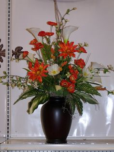 Calla lilies, Daisies and assorted foliage, this one is a large table piece, pending season, change out the colored flowers