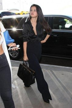 Selena Gomez dons plunging black silk blouse at LAX. Selena Gomez took the plunge in a silky black blouse for her flight out of LAX on … - Classy Outfits, Chic Outfits, Fashion Outfits, Womens Fashion, Women's Black Outfits, Black Slacks Outfit, All Black Outfit For Work, Selena Gomez Outfits, Selena Gomez Style